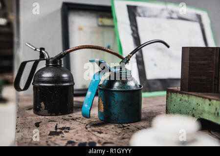 Two old metal container containing ball bearing grease placed on wooden table with engineering drawing in the background - Stock Photo