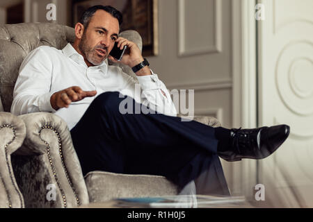 Mature traveler businessman wearing white shirt making call after arriving in the hotel room. Traveler sitting on couch and talking on smartphone. - Stock Photo