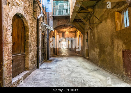 Old houses along narrow cobblestone street in medieval town Villefranche-sur-Mer on French Riviera, France - Stock Photo
