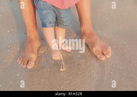 Man and baby feet standing in shallow water waiting for the wave. Bare feet father and his little daughter or son staying in the sand near the sea. Co - Stock Photo
