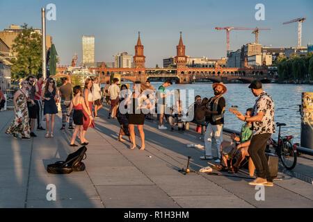 sunset at riverside Spree, Berlin wall, live band, background Oberbaum Bridge, Oberbaumbruecke, Friedrichshain, Berlin, Germany - Stock Photo