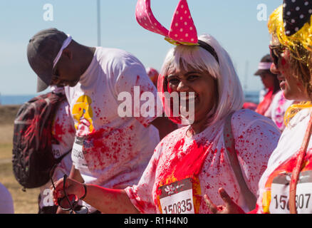 mixed race woman wearing a pair of pink polka dot bunny ears and blonde wig smiling at camera walking with group of friends in fun run sports event - Stock Photo
