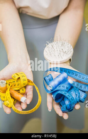 Sewing workshop. Seamstress at work. Closeup of hands holding a measuring tape - Stock Photo