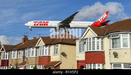 LONDON, ENGLAND - NOVEMBER 2018: LATAM Boeing 777 jet flying low over houses to land at London Heathrow Airport. - Stock Photo