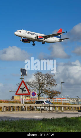 LONDON, ENGLAND - NOVEMBER 2018: Road sign on the A30 road at London Heathrow Airport warning motorists of low flying aircraft. In the background is a - Stock Photo