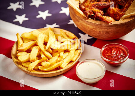 delicious fried chicken wings and french fries with background of the USA flag - Stock Photo