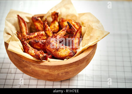 delicious fried chicken wings in a wooden bowl on a checkered tablecloth - Stock Photo