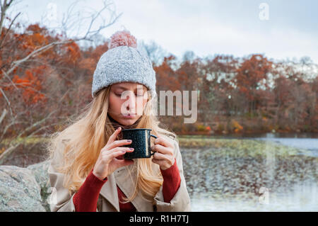 Beautiful woman in warm clothes and knitted hat drinking coffee in autumn park. Woman holding mug of coffee in the hands outdoor. - Stock Photo
