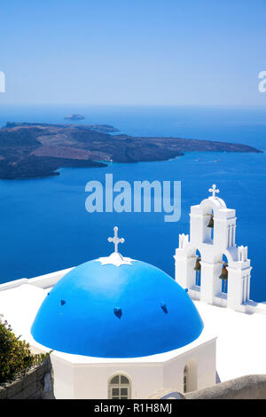 Church with blue dome roof and white bell tower at the crater rim, behind it the volcanic island Nea Kameni, Firofestani, Thira - Stock Photo