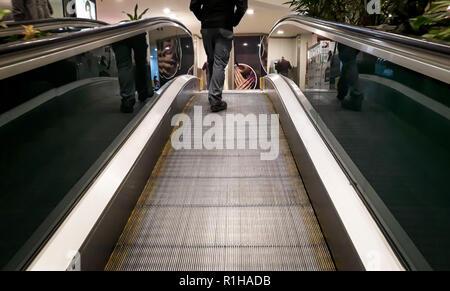 Man climbs escalator on shopping mall. Feet, shoes, Back view. - Stock Photo