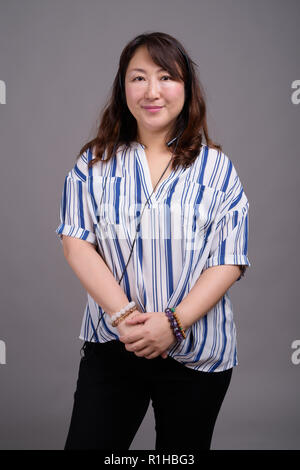Mature beautiful Asian businesswoman against gray background - Stock Photo