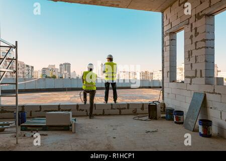 Two male builders at a construction site. Men looking into the distance to the panorama of the city. Building, development, teamwork and people concep - Stock Photo