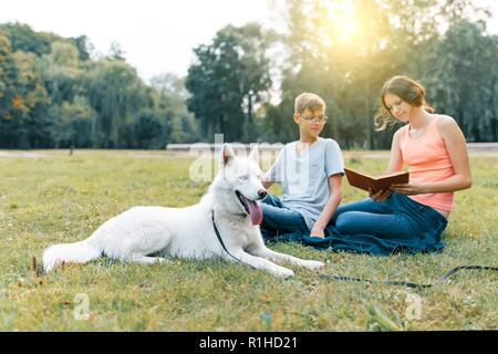 Children are resting in the park on green lawn with a white dog Husky, reading book, talking. - Stock Photo