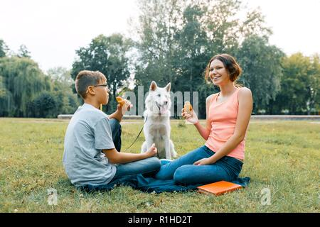 Children are resting in the park on green lawn with a white dog Husky, eating croissants, talking. - Stock Photo