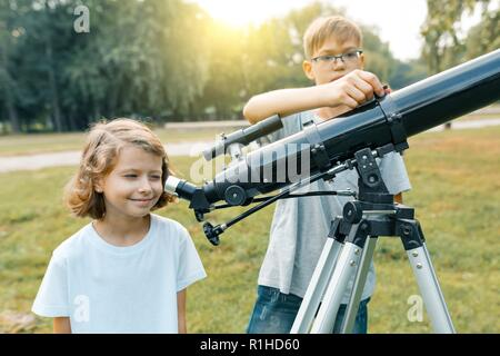 Children looking with interest in a telescope to the sky. - Stock Photo