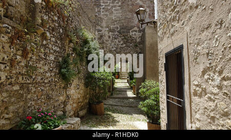 Narrow path between high stone walls and stone houses houses in Italy in Sicily - Stock Photo