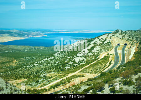 Two roads on a highway leading to tunnels in the Velebit mountain range among white rocks, green bushes and trees and azure blue sea water. Cloudless  - Stock Photo