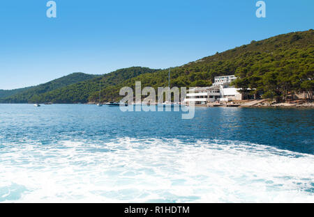 Vibrant blue sea with foam near the coast of an island and hills covered in green verdant forest. Several yachts in the water and a white house of a h - Stock Photo