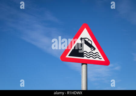 Highway code red triangle road sign in the United Kingdom warning motorists about the danger of a quayside or river bank. - Stock Photo