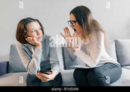 Teenager patient girl talking with professional psychotherapist in office. Girl looks into her phone ignores a psychologist - Stock Photo
