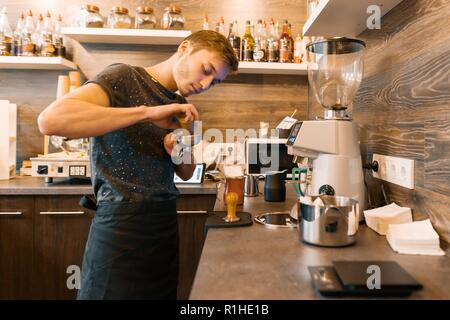 Portrait of young male barista making drinks. Coffee shop business concept. - Stock Photo