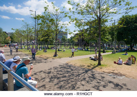 People sitting on steps enjoying the sunshine, Eyre Square, Galway, County Galway, Connacht, Ireland - Stock Photo