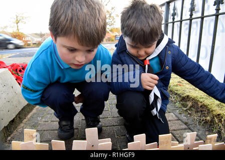 Youngsters perusing the crosses & poppies laid on Remembrance Sunday, War Memorial, Bordon, Hampshire, UK. 11.11.2018. - Stock Photo