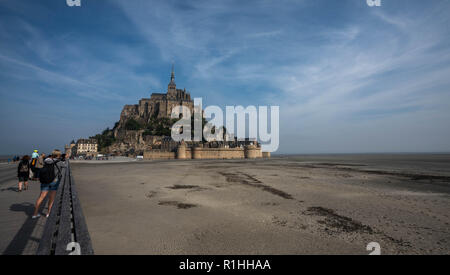 Landscape view of Mont Saint Michel during low tide and vast mud flats with tourists taking pictures. - Stock Photo
