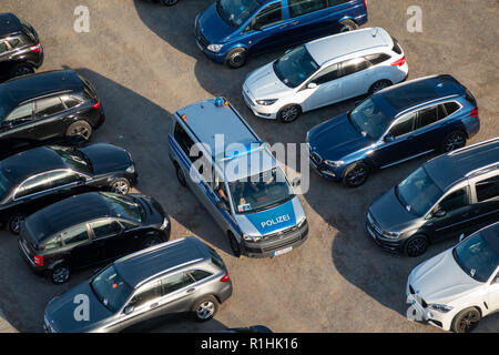 Hannover, Germany, October 6., 2018: A VW-Bully (Transporter of the brand Volkswagen) of the German police drives on a parking lot patrol, aerial phot - Stock Photo