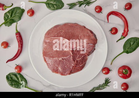 flat lay with fresh raw meat on plate with vegetables and herbs on white background - Stock Photo