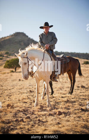 Portrait of a rancher sitting on a horse. - Stock Photo