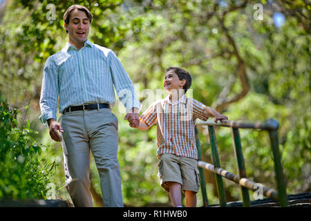 Happy father and son walking down stairs in a park. - Stock Photo