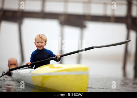 Young boy smiles as he holds an oar and sits in a kayak as a man pushes it along in the waters of a foggy harbour. - Stock Photo