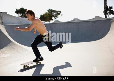Teenage boy skating at skate park - Stock Photo