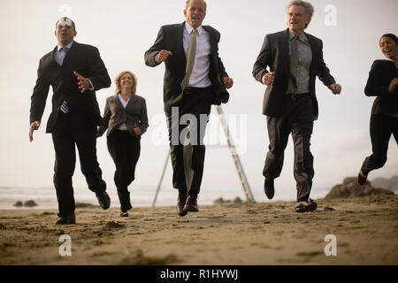 Colleagues running on beach - Stock Photo