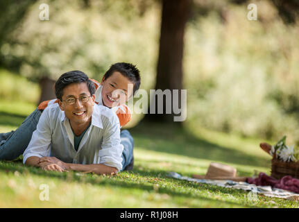Portrait of a smiling father and his young son lying in the park. - Stock Photo