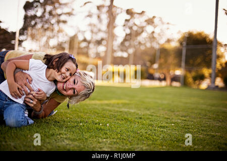 Girl and grandmother playing on grass in park - Stock Photo
