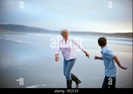Senior woman and her son running along the beach. - Stock Photo