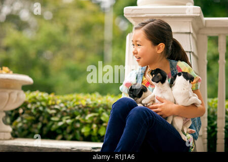 Smiling young girl holding three puppies in her lap. - Stock Photo