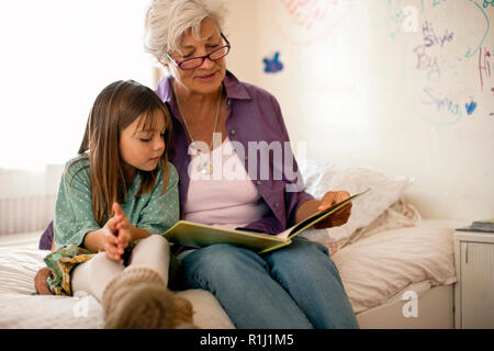 Grandmother reads a book with her young granddaughter as they sit together on a bed. - Stock Photo