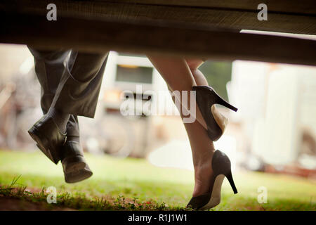 Dress shoes of a businessman and the high heels of his female colleague seen from under a park bench as they sit together. - Stock Photo