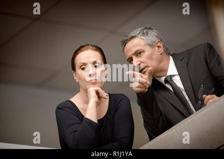 Serious businessman and a female colleague lean on the edge of an interior office balconey and look down as the businessman points to something below. - Stock Photo