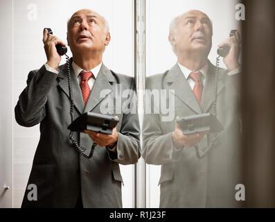 Senior businessman on a stressful phone call. - Stock Photo