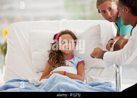 Young girl in a hospital bed,  talking with her doctor and nurse. - Stock Photo