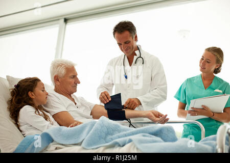 Elderly man receiving a hospital visit from his granddaughter while having his blood pressure taken. - Stock Photo