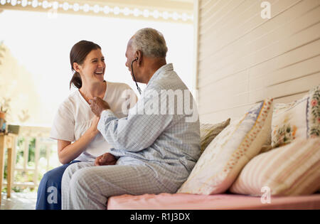 Elderly patient laughing while listening to the nurse's chest with stethoscope. - Stock Photo
