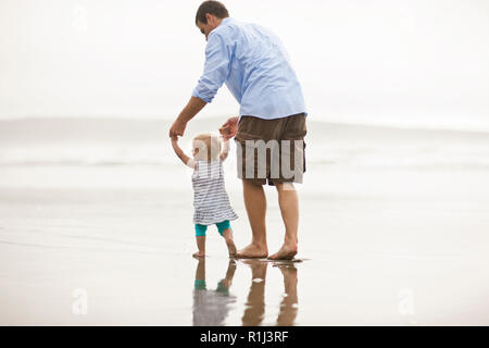 Father helping his baby daughter take her first steps on a beach. - Stock Photo