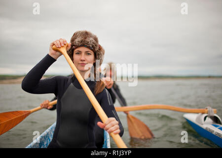 Portrait of a young woman wearing a fur hat and wetsuit while paddling in canoe with friends. - Stock Photo