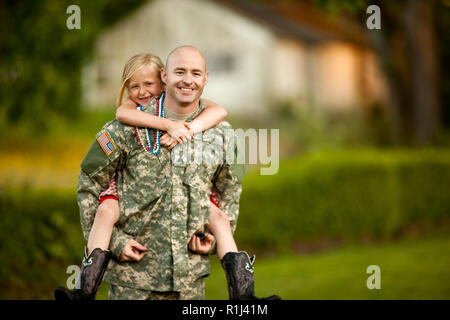 Smiling male soldier piggy-backing his young daughter in their back yard. - Stock Photo