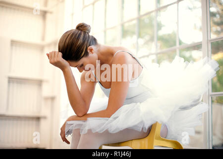 Mid adult ballerina sitting with her head in her hands. - Stock Photo